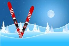 La scène bleue d'hiver des skis rouges se tenant dans la neige a couvert des collines sous un ciel allumé par lune photos stock