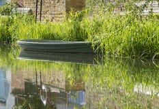 La scène tranquille de rivière avec le bateau à rames vide a amarré à la banque Photographie stock libre de droits