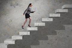 La scala rampicante di carriera della giovane donna di affari Immagine Stock