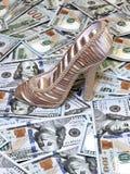 La scarpa delle donne su un fondo delle fatture di dollari americani Fotografia Stock