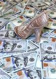 La scarpa delle donne su un fondo delle fatture di dollari americani Immagine Stock