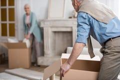 La scatola di cartone della tenuta dell'uomo e la moglie d'aiuto disimballano le cose fotografie stock