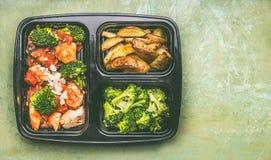 La scatola di pranzo equilibrata sana con il pollo collega in salsa di pomodori con i broccoli verdi e le patate al forno Fotografie Stock Libere da Diritti