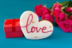 La scatola di regalo ed il mazzo di rose e pan di zenzero sotto forma di cuore con l'iscrizione amano per la festa su di legno Immagini Stock Libere da Diritti