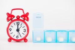 La scatola settimanale della pillola e l'orologio rosso mostrano il tempo della medicina Fotografie Stock