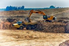 La scavatrice carica la terra nel camion fotografia stock