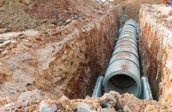 La scavatura e la fila di drenaggio concreto convogliano su un cantiere Il sistema di acque reflue impilato tubo concreto ha alli fotografia stock libera da diritti