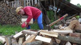 La scelta dell'uomo dell'agricoltore ha tagliato la legna da ardere in capriata e la pila a pezzi vicino alla legnaia 4K archivi video