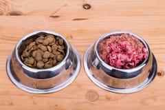 La scelta di carne cruda o macina grosso il cibo per cani in ciotola Immagini Stock