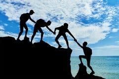 La scena concettuale degli alpinisti maschii funziona in un gruppo Immagine Stock Libera da Diritti