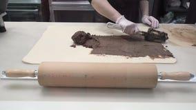 La scena: Cucini gli smeets il materiale da otturazione con la cannella sullo strato della pasta Produzione dei rotoli di cannell stock footage