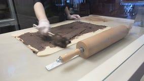 La scena: Cucini gli smeets il materiale da otturazione con la cannella sullo strato della pasta Produzione dei rotoli di cannell archivi video