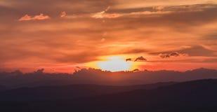 La scena del tramonto con la caduta del sole ed il raggio si accendono, nuvole nel fondo, Fotografia Stock