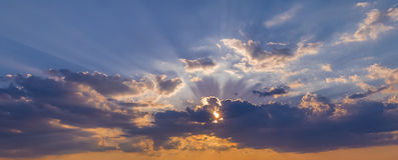 La scena del tramonto con la caduta del sole ed il raggio si accendono, nuvole nel fondo, cielo variopinto caldo Immagini Stock