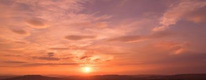 La scena del tramonto con la caduta del sole ed il raggio si accendono, nuvole nel fondo, cielo variopinto caldo Fotografia Stock