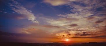 La scena del tramonto con la caduta del sole ed il raggio si accendono, nuvole nel fondo, cielo variopinto caldo Immagine Stock