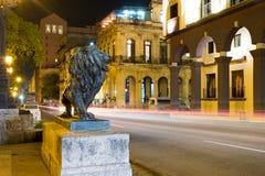 La scena di notte a vecchia Avana con un leone bronzeo famoso ha considerato un simbolo della città fotografie stock
