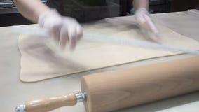 La scena: Il cuoco allinea la pasta sulla tavola per mezzo delle mani, modellanti la pasta Produzione dei rotoli di cannella stock footage