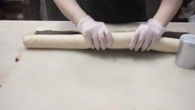 La scena: Il cuoco avvolge la pasta con cannella che farcisce in un rotolo Produzione dei rotoli di cannella Prodotti del forno a stock footage