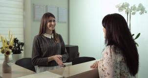La scena nella femmina paziente felice e sorridente dell'ufficio del dentista ha conversazione con il dentista, discute il tratta stock footage