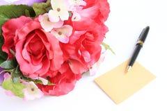 La scheda in bianco con la penna ed è aumentato Fotografia Stock