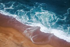 La schiuma giallo sabbia di azzurro e della spiaggia ondeggia, sparato da sopra, natura o fotografia stock