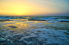La schiuma ondeggia sulla costa di mare durante l'alba Fotografia Stock