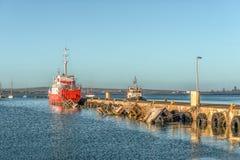 La sciabica di pesca e la barca incavata al tramonto in Saldanha abbaiano immagine stock libera da diritti