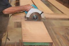 La scie circulaire électrique contre la sciure est coupée un morceau de bois à la main de charpentier supérieur dans le woodshop  Photos stock
