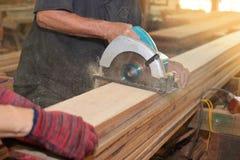 La scie circulaire électrique est coupée un conseil en bois par des travailleurs dans la boutique de boisage Photo libre de droits