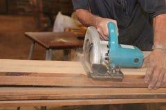 La scie circulaire électrique est coupée un conseil en bois par des travailleurs dans la boutique de boisage Images libres de droits