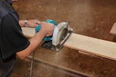 La scie circulaire électrique est coupée un morceau de bois contre des mains de charpentier supérieur dans l'atelier de menuiseri Image libre de droits