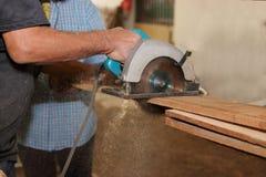 La scie circulaire électrique est sciée avec un morceau de bois par un charpentier supérieur dans l'atelier de menuiserie Image libre de droits