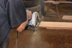 La scie circulaire électrique est sciée un morceau de bois par le travailleur supérieur dans l'atelier de menuiserie Images libres de droits