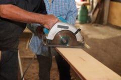 La scie circulaire électrique est sciée un morceau de bois par le travailleur supérieur dans l'atelier de menuiserie Photo libre de droits