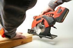 La scie de circulaire portative dans les mains d'un travailleur scie un conseil en bois sur un fond blanc image libre de droits