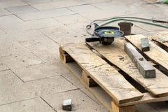 La scie de circulaire pour scier d'un plat de frontière se trouve sur une palette en bois à la construction des trottoirs photos stock