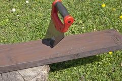 La scie et le panneau en bois Photographie stock