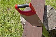 La scie et le panneau en bois Photographie stock libre de droits