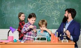 La Science est toujours la solution Observez la r?action Exp?rience de chimie d'?cole Le?on fascinante de chimie Homme barbu photo stock
