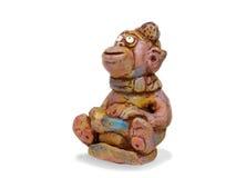 La scimmia allegra dalle terraglie dell'argilla si siede sulla slitta Fotografia Stock
