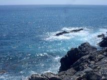La scogliera e le onde che si schiantano su nei mari di Genova Immagini Stock Libere da Diritti