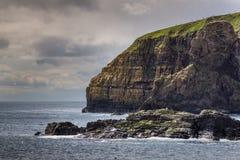 La scogliera enorme discende nel Mare del Nord a Lybster, Scozia Immagine Stock