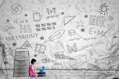 La scolara adorabile si siede vicino ad un mucchio dei libri tirati Immagine Stock