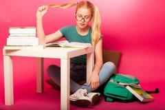 La scolara allegra con i grandi occhiali si è concentrata in b leggente Fotografia Stock