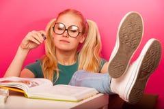 La scolara allegra con i grandi occhiali si è concentrata in b leggente Fotografie Stock
