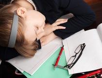 La scolara caucasica bionda dorme sullo scrittorio Immagini Stock