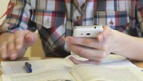 La scolara che si siede ad uno scrittorio tiene uno smartphone stock footage