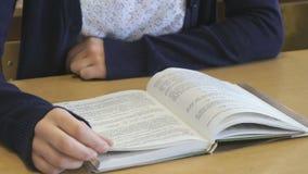 La scolara che si siede allo scrittorio della scuola legge il libro stock footage