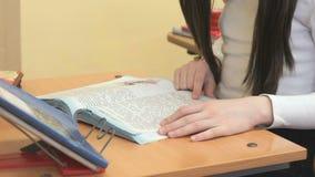 La scolara che si siede allo scrittorio della scuola legge il manuale stock footage